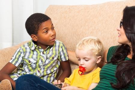 garcon africain: Détail de la jeune femme parlant avec des enfants sur le canapé. Banque d'images