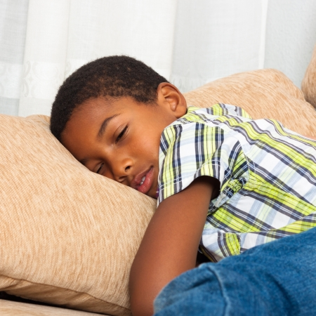 Close up of cute tired child boy sleeping on sofa.