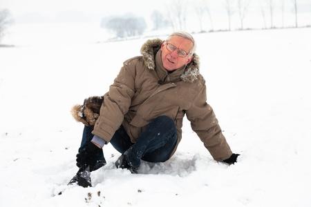Unhappy senior man with injured painful leg on snow. Stockfoto