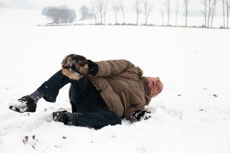lesionado: Hombre mayor con la pierna lesionada que cae sobre la nieve.