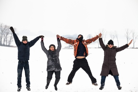 happy people jumping: Group of young happy people jumping in snow and enjoying winter. Stock Photo