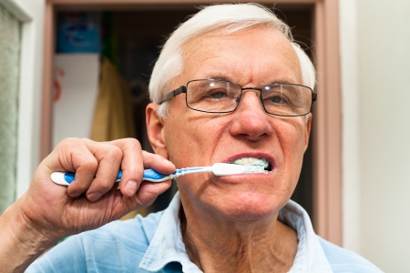 Close up of senior man brushing his teeth. photo