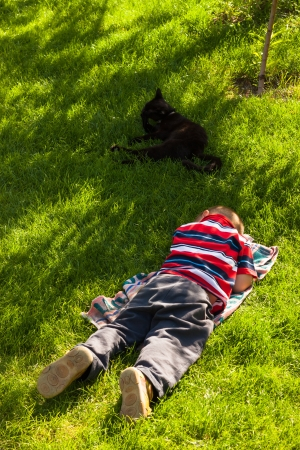 Tired child boy sleeping in green grass. photo