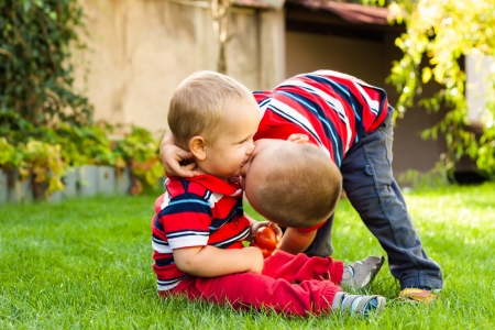 Two little happy brothers kissing outdoors. photo