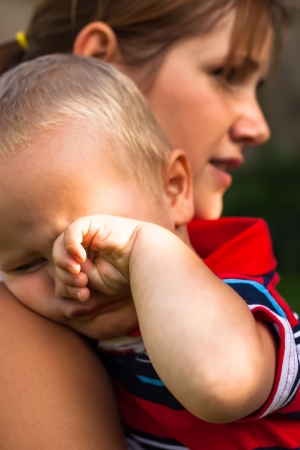 Portrait of cute crying toddler and his mother. photo