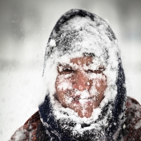 Man covered by snow in heavy snowstorm. Stock Photo