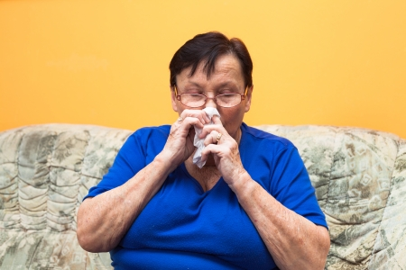 Sick senior woman sitting on sofa and blowing her nose. photo