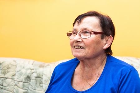 Happy smiling senior woman sitting on sofa over yellow background. photo