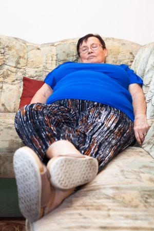 Obese elderly casual woman sleeping on sofa. photo