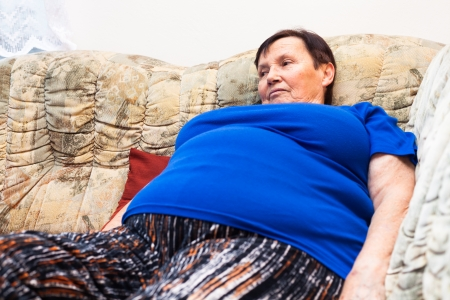Close up of obese elderly woman relaxing on sofa. Stockfoto