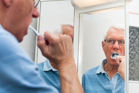 toothbrushing: Close up of senior man reflected in mirror brushing his teeth.