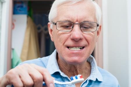toothbrushing: Close up of senior man going to brush his teeth.