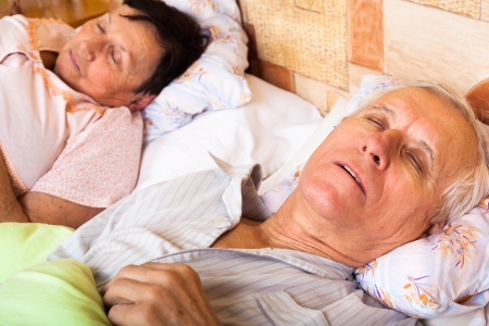 Close up of senior couple sleeping in bed. photo