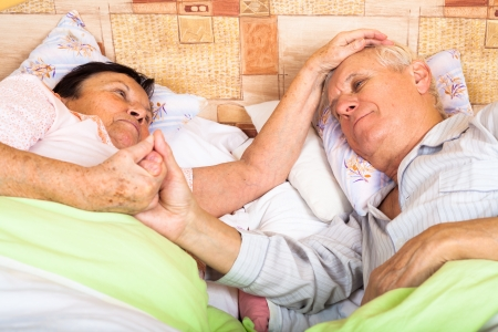Close up of loving senior couple relaxing in bed. photo