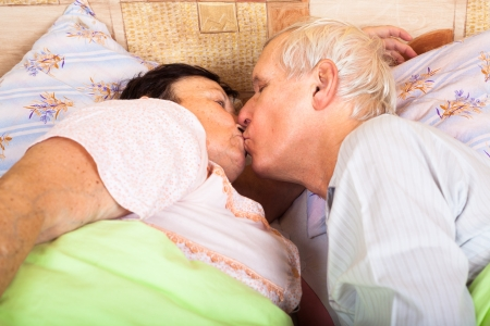 Close up of loving senior couple kissing in bed. photo