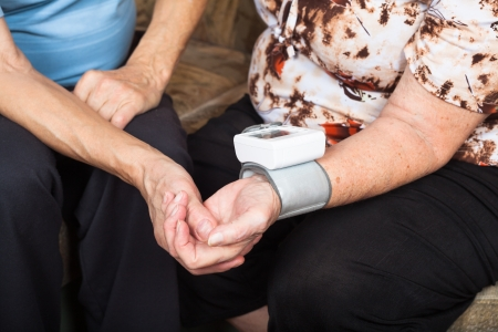 heart monitor: Close up of two seniors checking blood pressure.