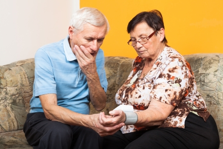 Two worried seniors checking blood pressure at home. photo