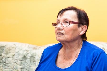 Smiling elderly woman sitting on sofa over yellow background. photo
