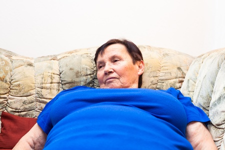 Close up of obese elderly woman lying on sofa.