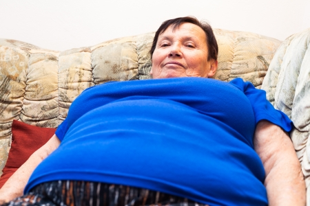 Close up of happy obese elderly woman relaxing on sofa.