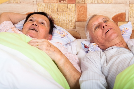 Close up of happy senior couple resting in bed at home. photo