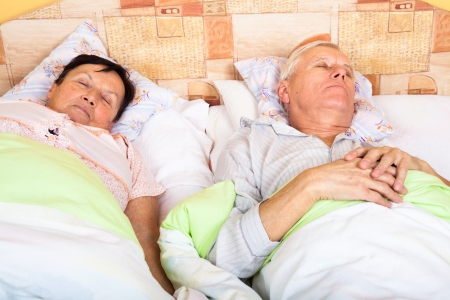 Close up of senior man and woman sleeping in bed. photo
