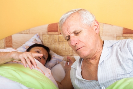 Unhappy tired senior couple in bed waking up.