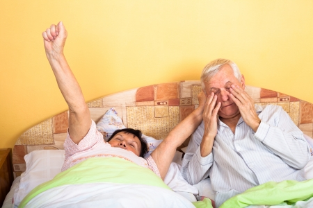 Senior couple in bed stretching and waking up. photo