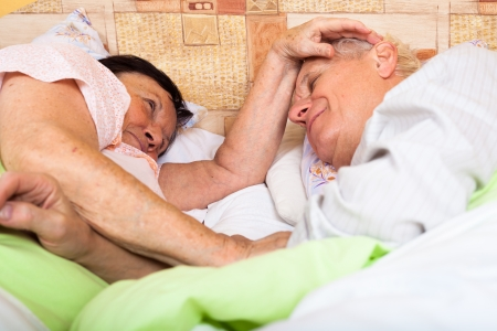 Close up of happy loving senior couple relaxing in bed. photo