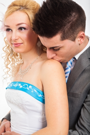 rumanian: Close up of wedding couple hugging and kissing on shoulder.