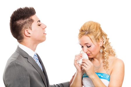 rumanian: Wedding portrait of serious groom and unhappy bride crying, isolated on white background.