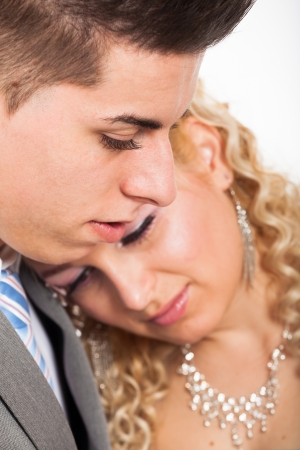 rumanian: Close up of young beautiful loving wedding couple embracing.