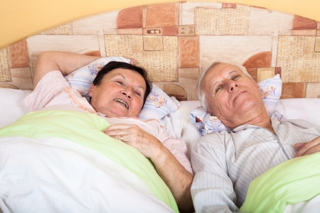 Close up of happy senior couple resting in bed. photo