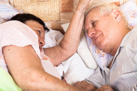 Detail of senior couple relaxing in bed. photo