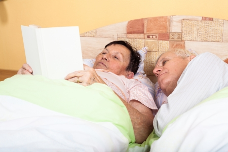 Close up of two seniors reading book in bed. photo