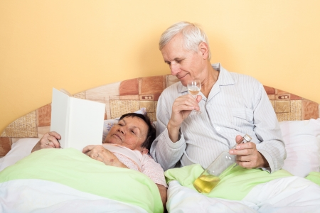 Funny senior man drinking alcohol and woman reading book in bed photo