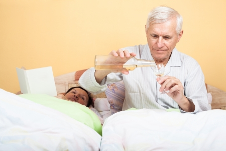 Senior man with bottle of alcohol and woman elderly with book in bed photo