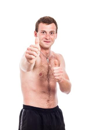 niño sin camisa: Hombre sin camisa joven que muestra los pulgares para arriba, aislado en fondo blanco Foto de archivo