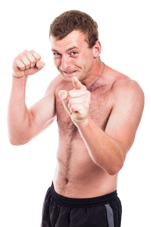 Young furious shirtless man showing fist and pointing at you, isolated on white background photo