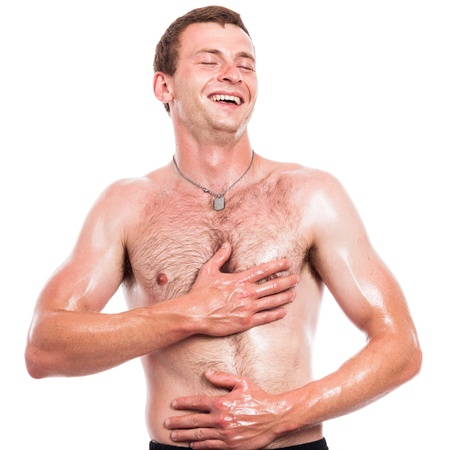body oil: Ecstatic shirtless man touching his body, isolated on white background Stock Photo