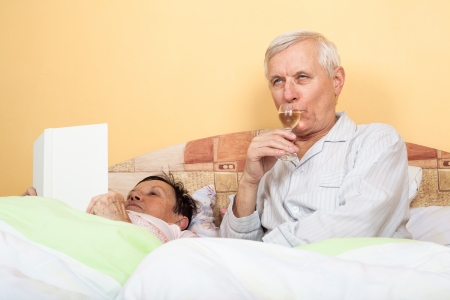 Senior couple in bed drinking alcohol and reading book photo
