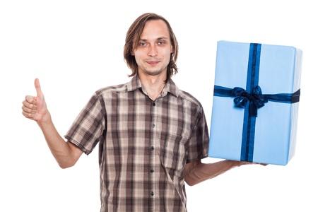 weirdo: Happy man holding big blue gift box showing thumb up, isolated on white background