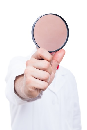 Scientist in lab coat with magnifying glass, isolated on white background Stock Photo