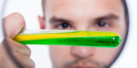 Closeup of man with magnifying glass and test tube photo