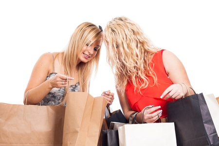 Two happy blond girls looking inside shopping bags, isolated on white background photo