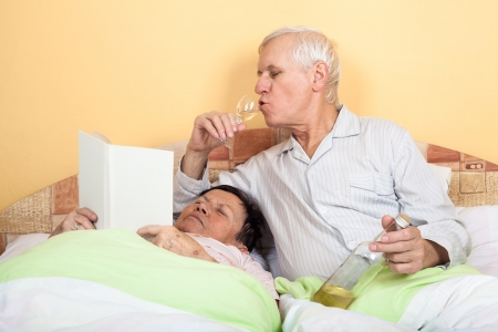 Funny senior couple relaxing in bed with alcohol and book photo