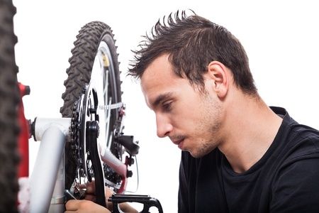 Young man repairing bicycle, isolated on white background