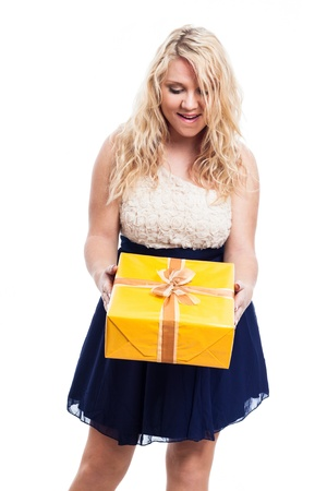 Portrait of happy surprised woman holding yellow gift box, isolated on white background photo
