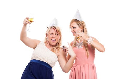 Two ecstatic girls celebrate with alcohol, isolated on white background photo