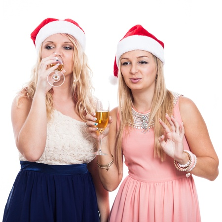 Two Christmas women partying with glass of alcohol, isolated on white background photo